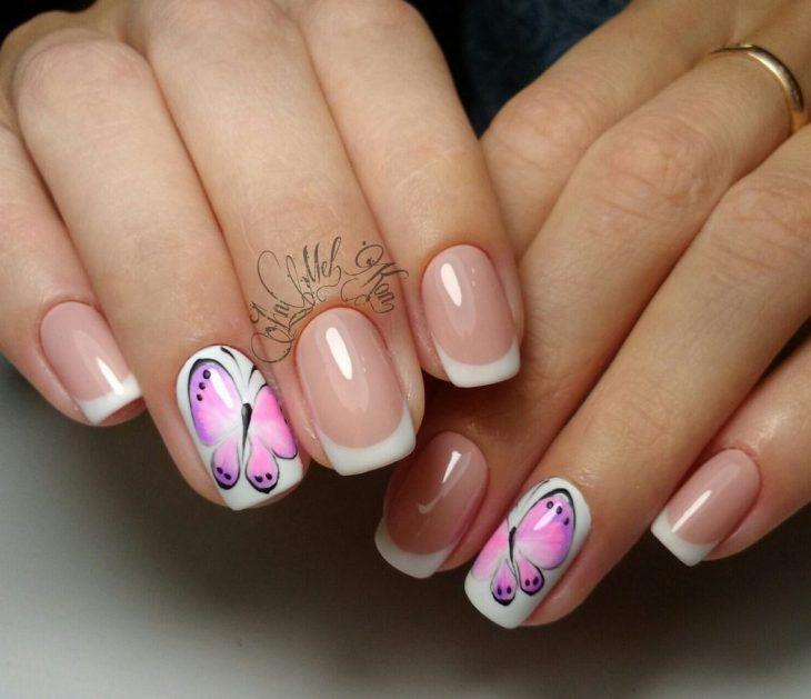 Uñas pintadas con esmalte blanco y transparente con diseño de mariposas