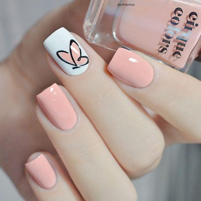 Uñas pintadas con esmalte color coral y blanco con diseño de mariposa minimalista