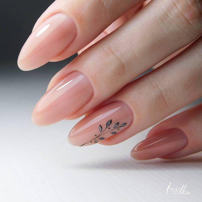 Uñas pintadas con esmalte colo rosa claro con diseño de flor minimalista