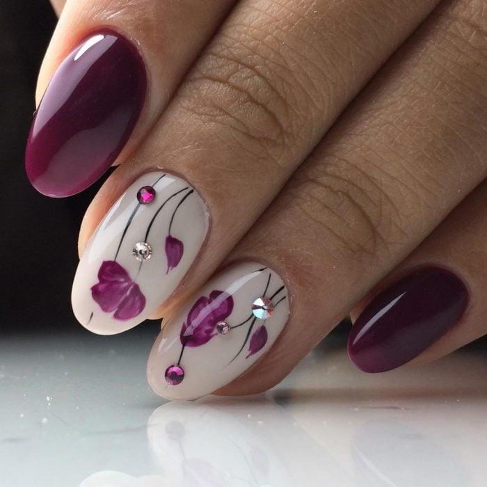 Uñas pintadas con esmalte morado y blanco con diseño de flores y puntos