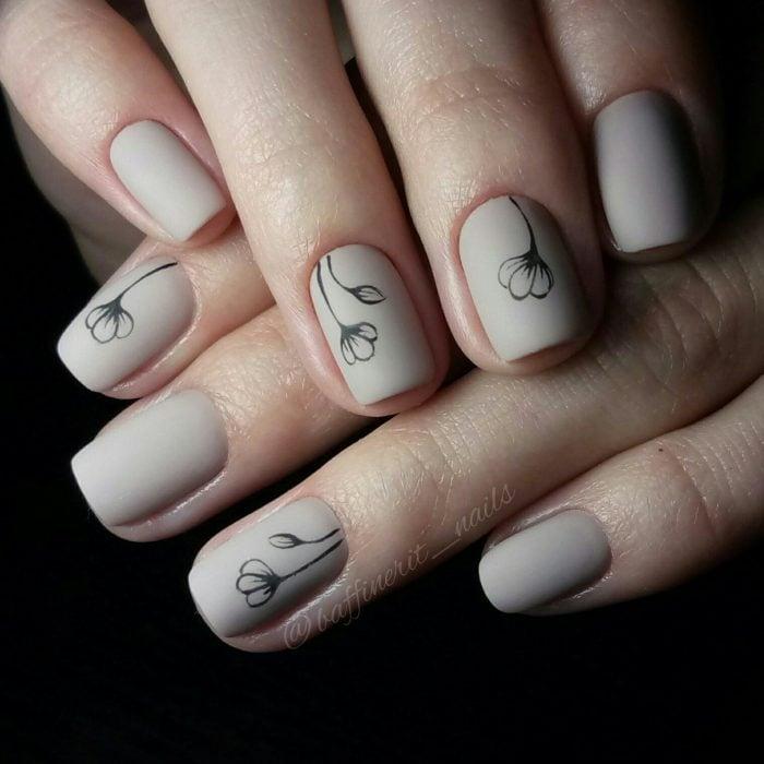 Uñas pintadas con esmalte color gris y diseño de flores minimalistas