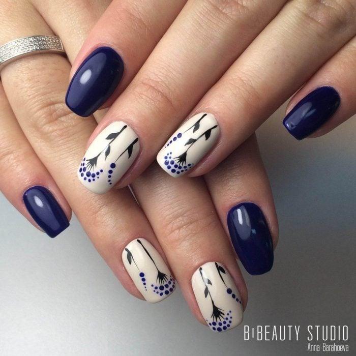 Uñas pintadas de azul y blanco con diseño de flores y puntos