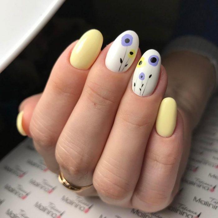 Uñas pintadas de amarillo y blanco con diseño de flores y puntos
