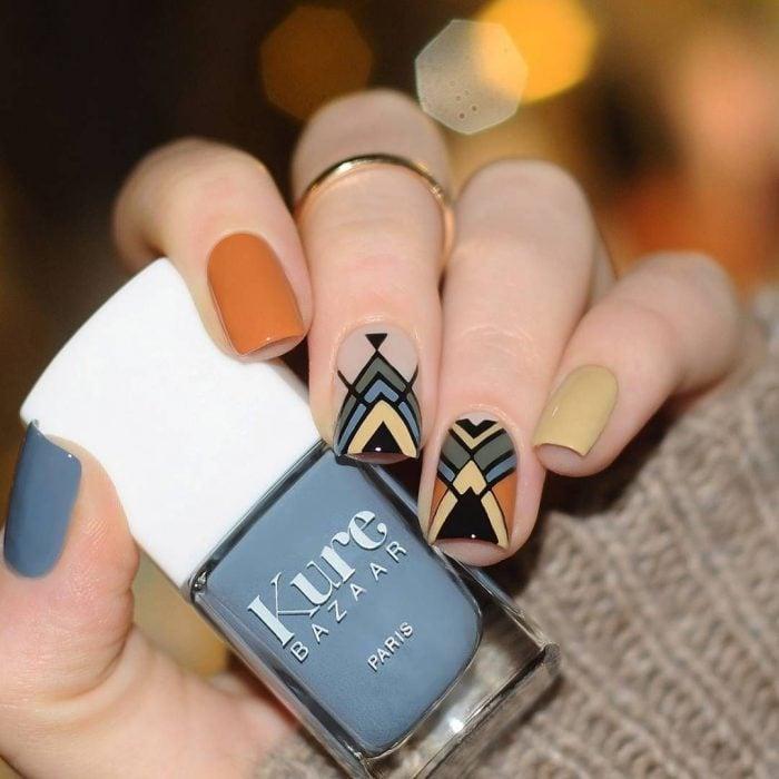 Uñas pintadas de anaranjado y gris con diseño de líneas y triángulos