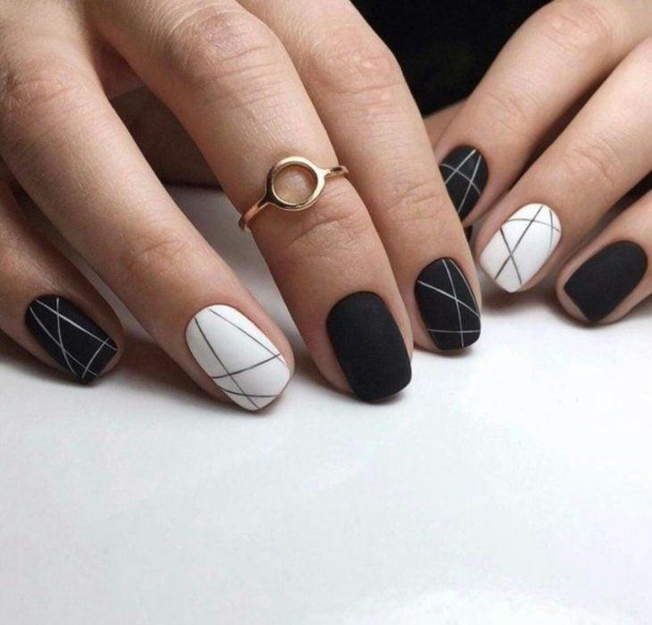 Uñas pintadas de negro y blanco con diseño de líneas rectas minimalistas