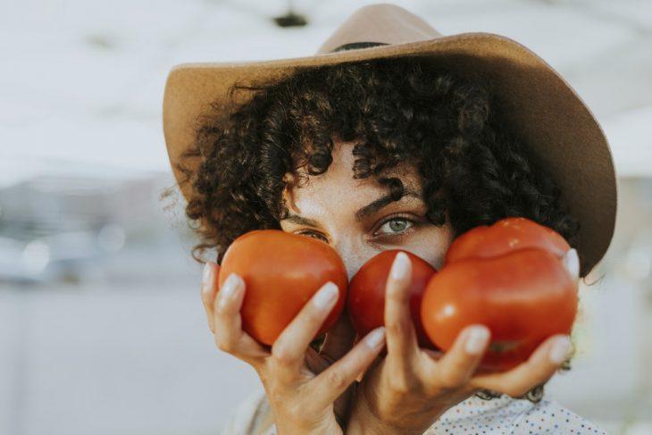 chica sosteniendo tomates en sus manos