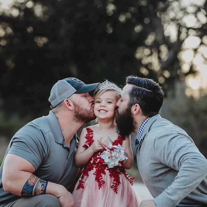 Niña posando junto a su padre y al prometido de su mamá