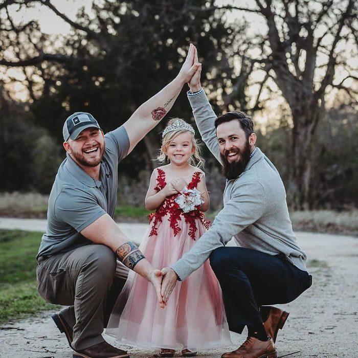 Pareja mixta abrazando a su hija de 4 años