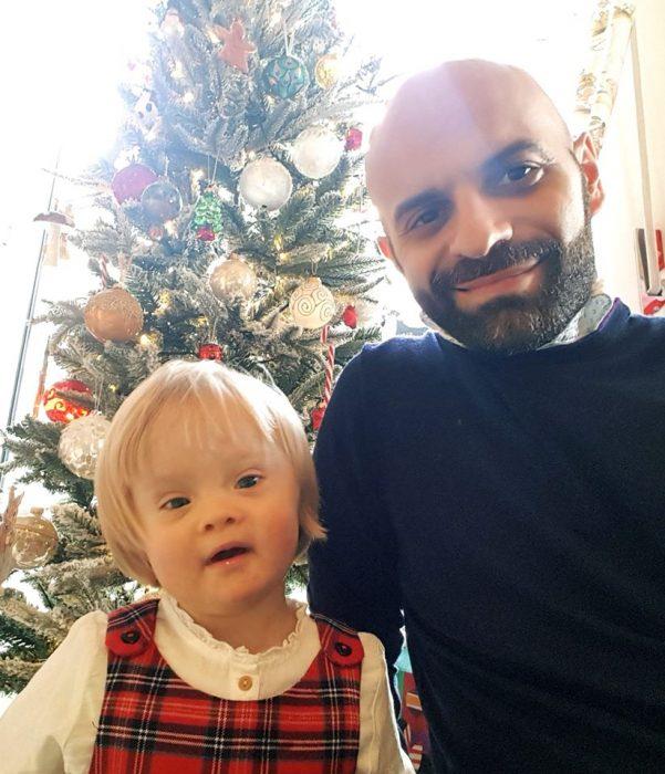 Luca Trapanese posando junto a su hija alba a un lado del árbol de navidad