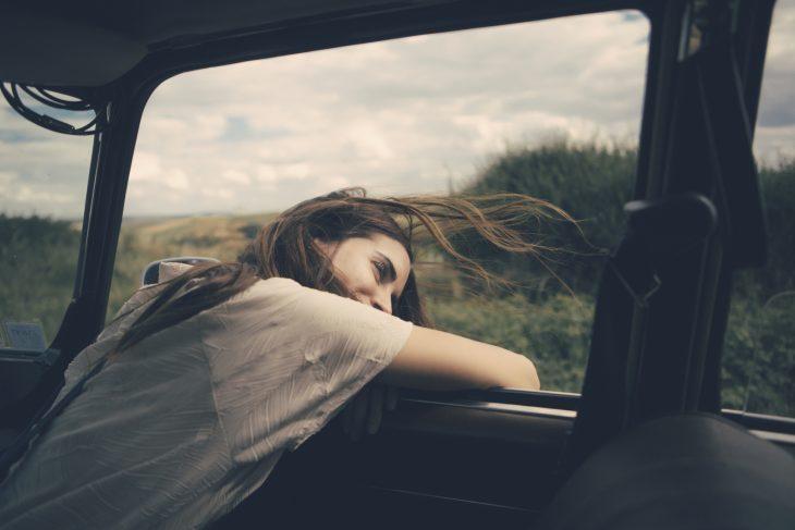 Chica de cabello castaño y despeinado mira por la ventana de un carro