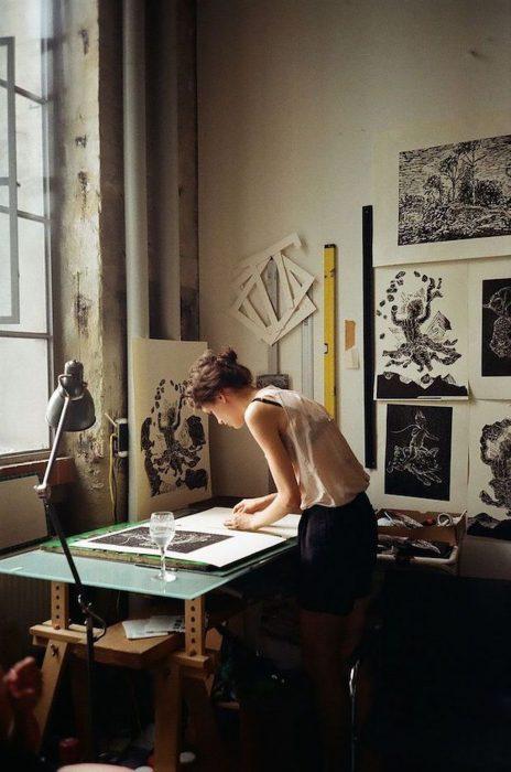 Chica dibujando en escritorio con una copa de agua