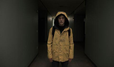 chico llevando un impermeable amarillo