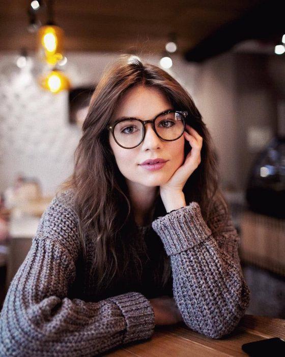Chica de cabello castaño, largo y suelto, con lentes de aumento y suéter gris tejido
