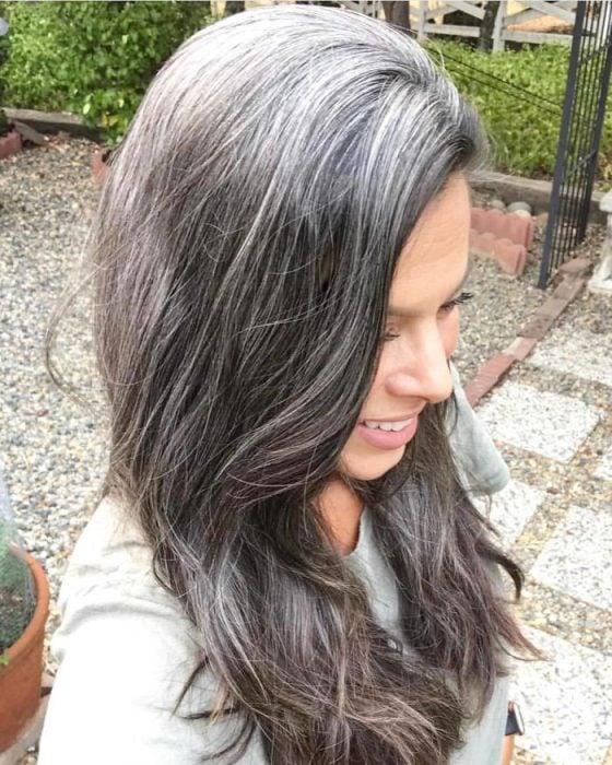 Mujer presumiendo su cabello con canas