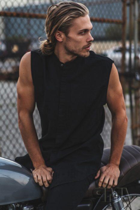 Hombre nórdico de cabello rubio y largo, sobre una motocicleta