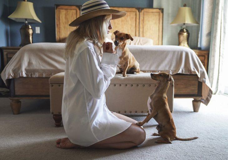 chica cuidando a sus perros en casa