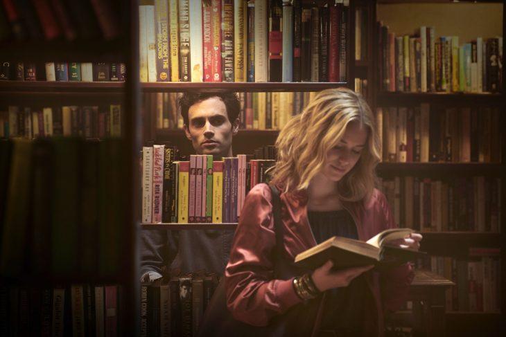 Chico de cabello negro mirando de lejos a una chica que lee un libro en una biblioteca