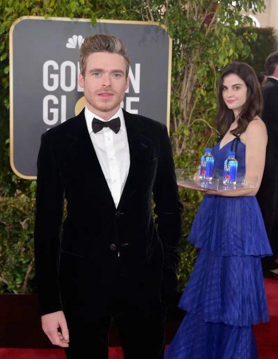 hombre en alfombra roja y mujer con vestido azul atrás