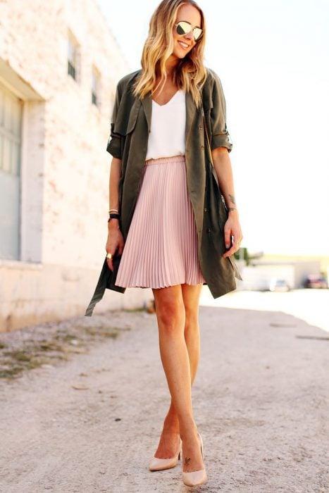mujer con chamarra verde militar y falda rosa pastel