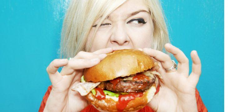 mujer rubia comiendo una hamburguesa