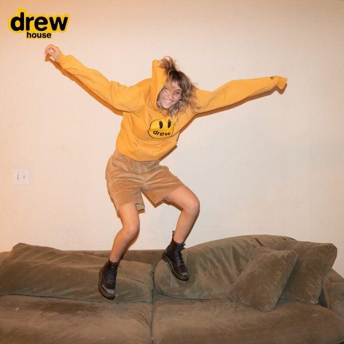 hombre con cabello rubio y sudadera amarilla saltando en sillón