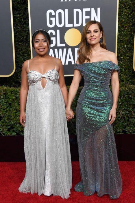 mujer morena con vestido plata y mujer con vestido verde rubia