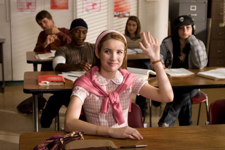 niña vestida de rosa con sueter en salon de clases