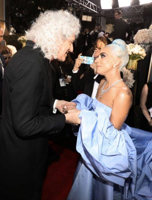 mujer con vestido lila y hombre con cabello blanco