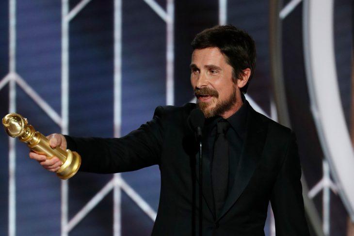 hombre con ropa negra y globo de oro