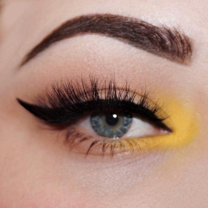 ojos azules con delineador y sombra amarilla