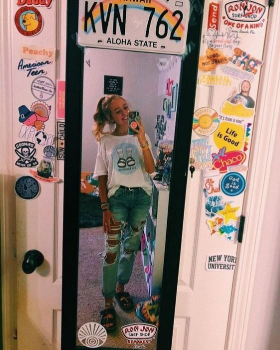 mujer frente a espejo con estampas en la puerta