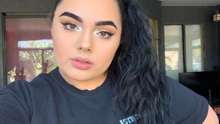 mujer con maquillaje cabello negro y lagrimal azul