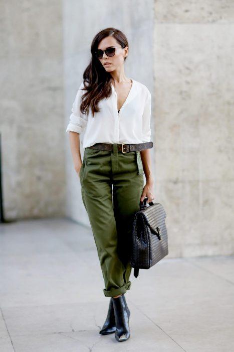 mujer con pantalón verde y camisa blanca