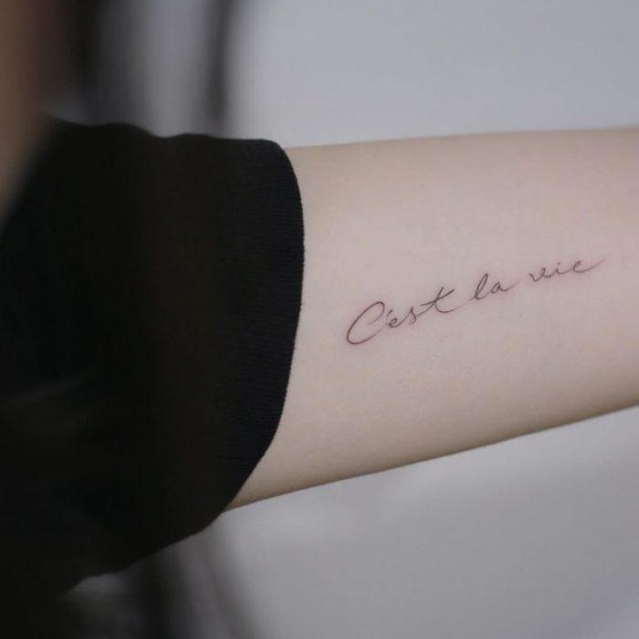 mujer con tatuaje de frase en el brazo