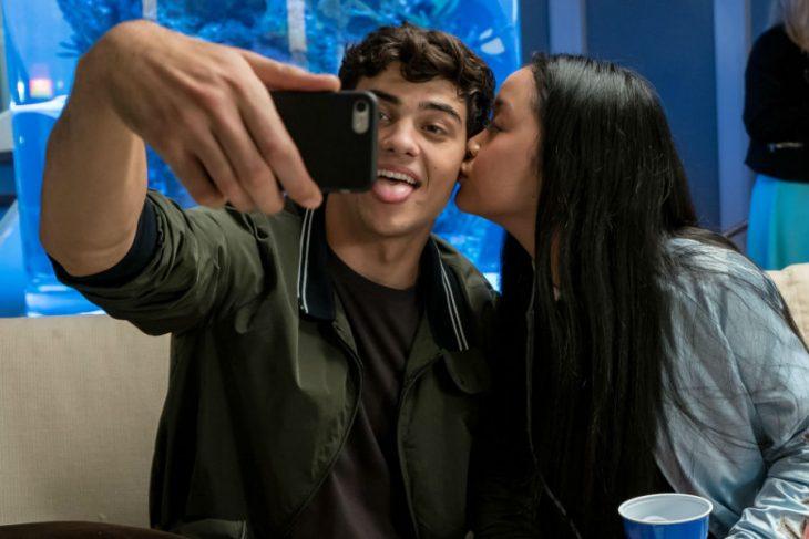 hombre con celular tomando selfie y mujer besandolo