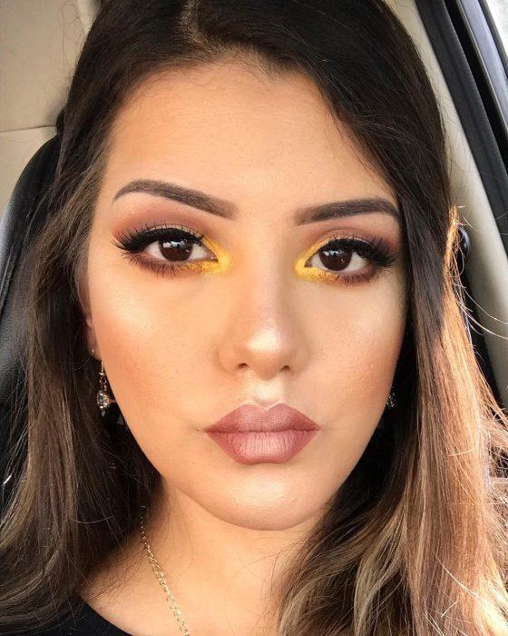 mujer con maquillaje amarillo en el lagrimal