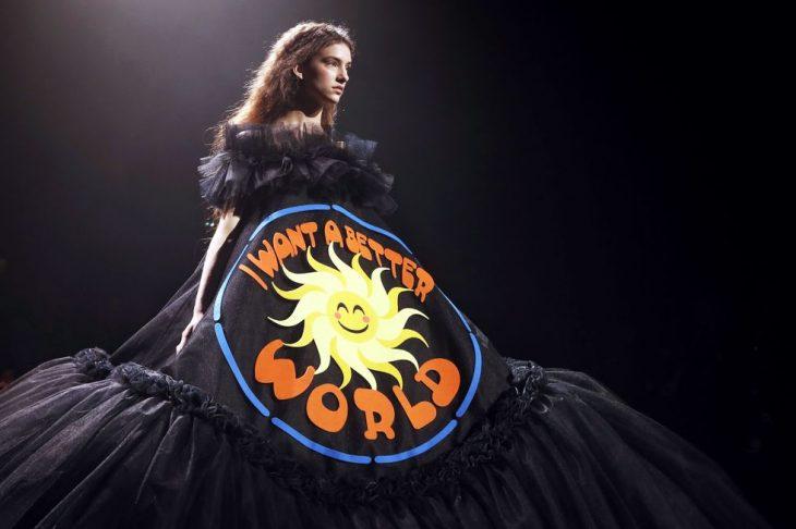 mujer pasarela de modas con vestido color negro con letras naranjas