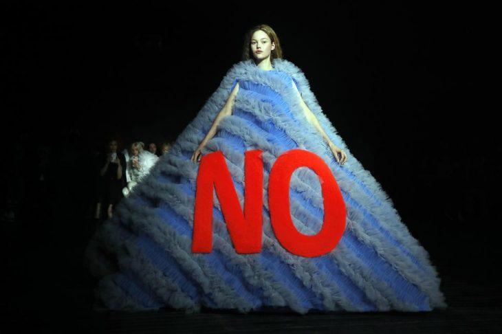 mujer pasarela de modas con vestido color azul con letras roja