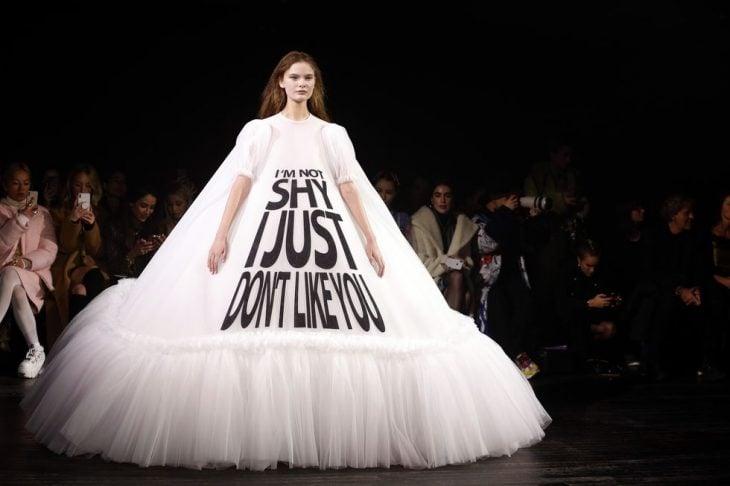 mujer pasarela de modas con vestido color blanco letras