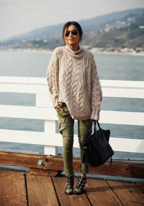 mujer con sueter grande tejido y pantalones militares