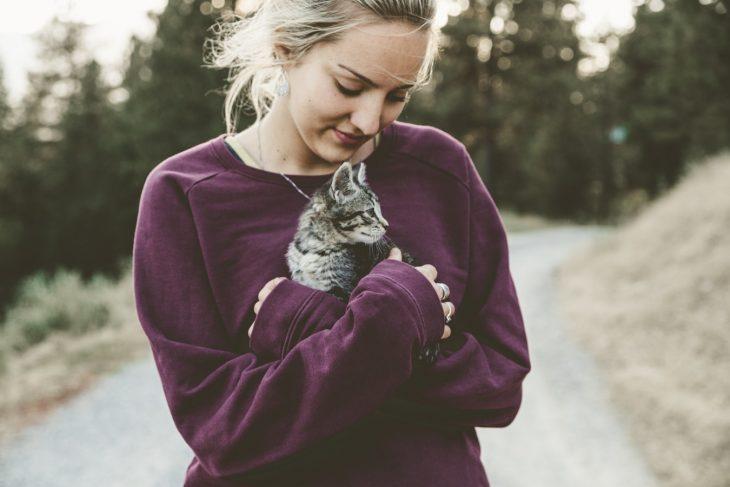 chica cargando un gato pequeño