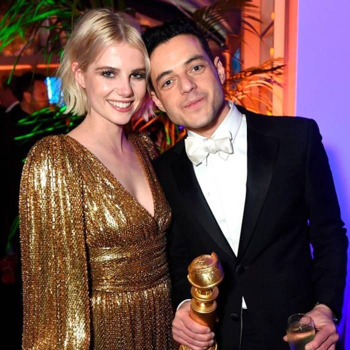 mujer con vestido dorado y hombre con traje negro y globo de oro