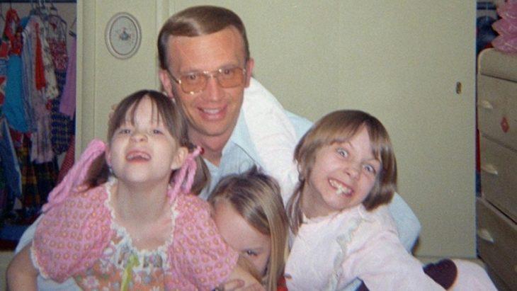 hombre abrazando a unas niñas
