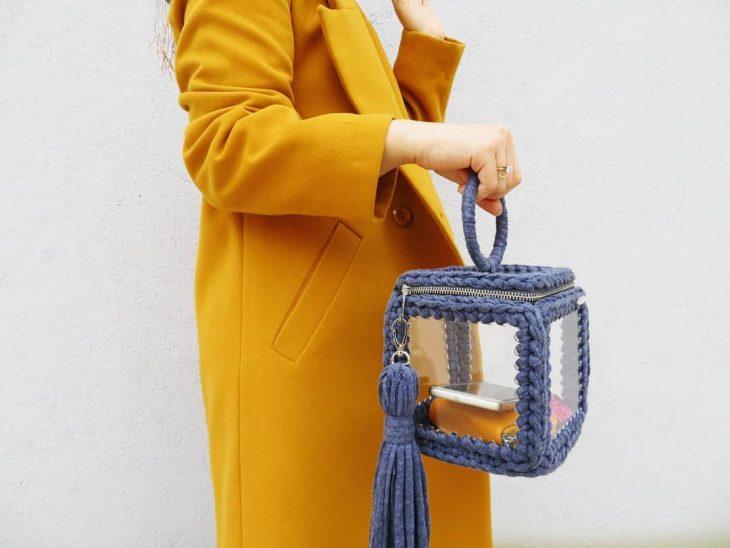 mujer con saco amarillo y boslo gris con caja transparente