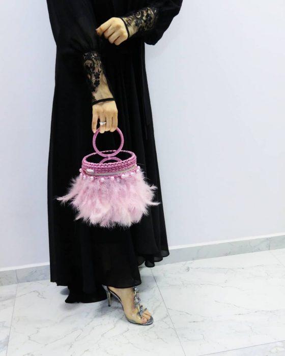 mujer con bolso rosa de plumas