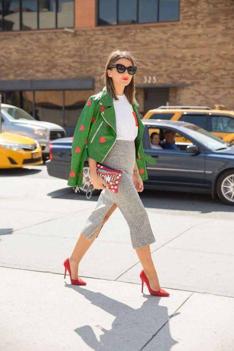 Chica vestida de manera elegante mientras posa para una foto en la calle
