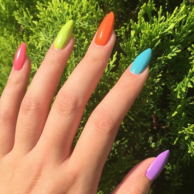 manos de mujer con uñas de colores arcoiris
