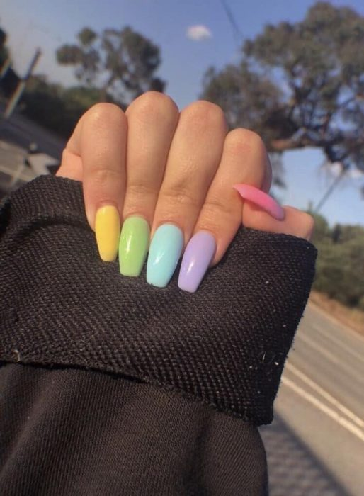manos de mujer con uñas de colores