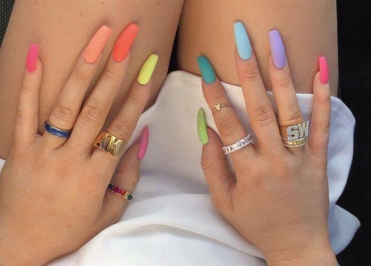 manos de mujer con uñas de colores pastel