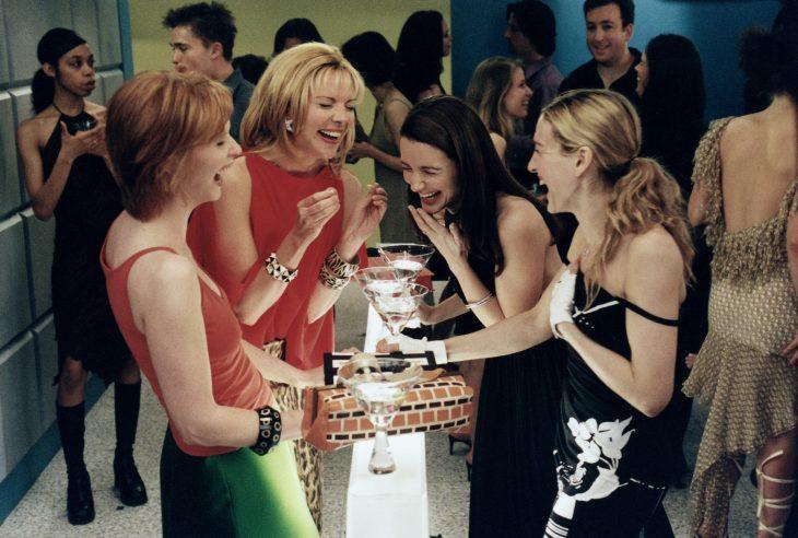 Grupo de amigas bebiendo y riendo en una fiesta